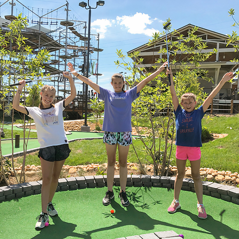 Three girls with their hands up high having fun at Soar Adventures