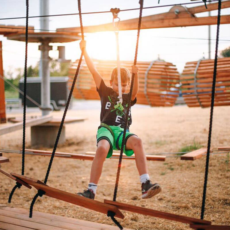 Kid hanging to a rope in adventure park