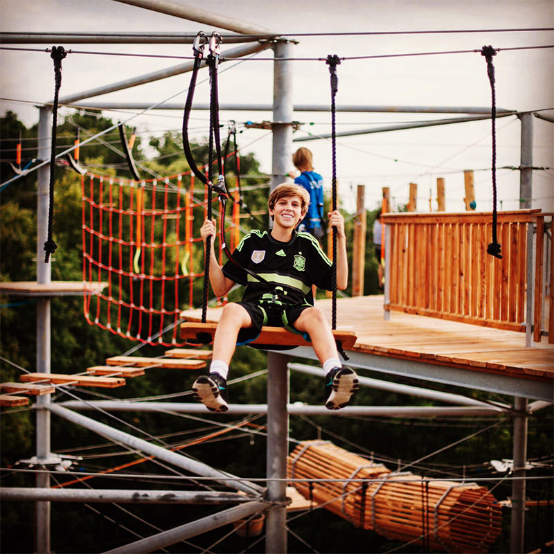 Boy sitting on top of adventure tower